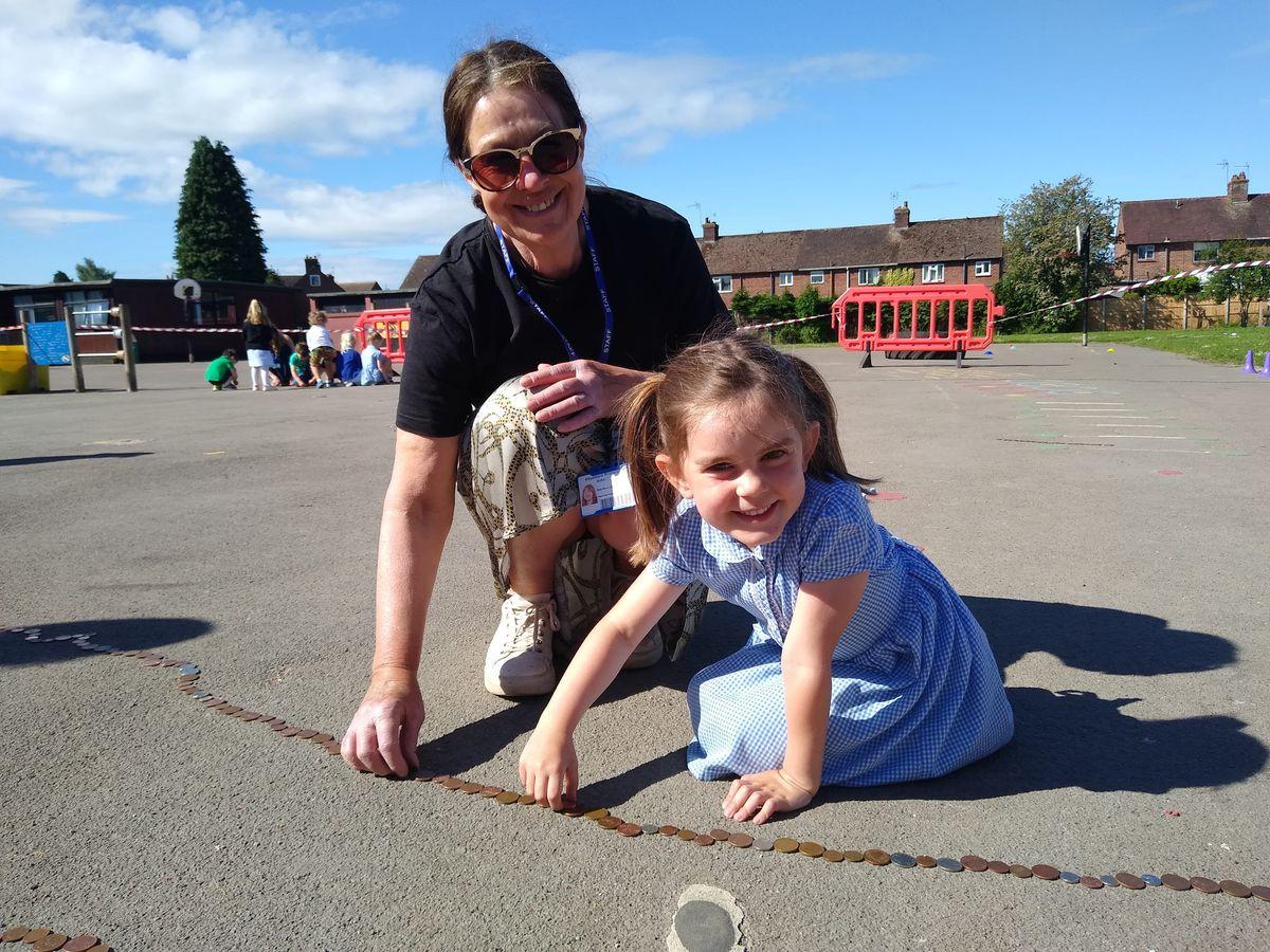 Sue McBride helps Emily Wilsmer create the snake of coins