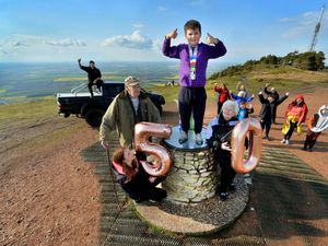Ryley McGlinn, eight, gives everyone a big thumbs up after completing his 50th walk up The Wrekin in aid of charity