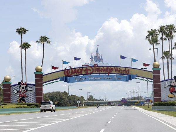 Cars drive under a sign greeting visitors near the entrance to Walt Disney World, in Lake Buena Vista, Florida (Jon Raoux/AP)