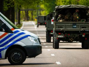Belgian military ride in a convoy at the entrance of the National Park Hoge Kempen during a manhunt for an armed soldier in Maasmechelen, Belgium (Francisco Seco/AP)