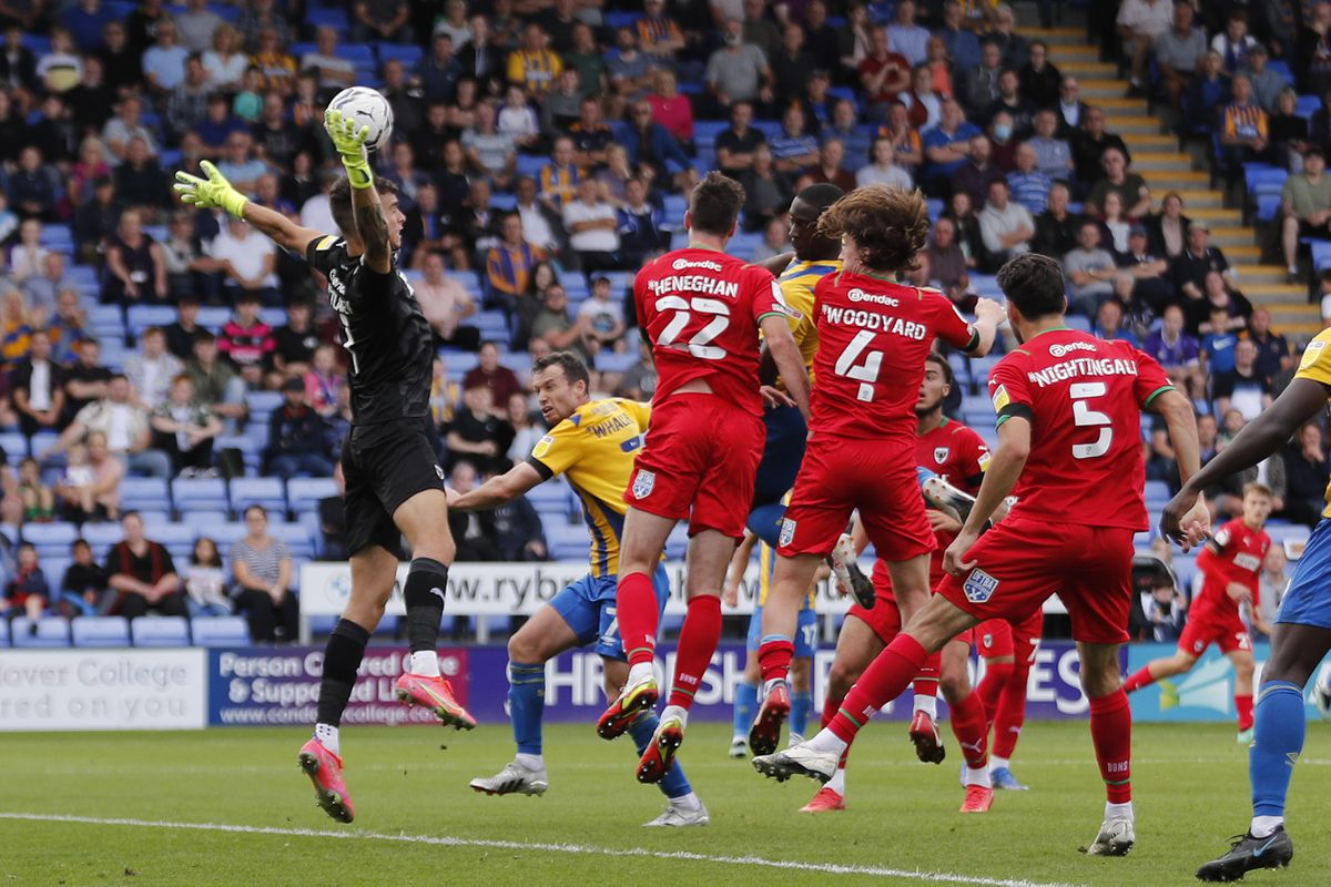 Dan Udoh gets in front of Dons keeper Nik Tzanez to head in the winner (AMA)