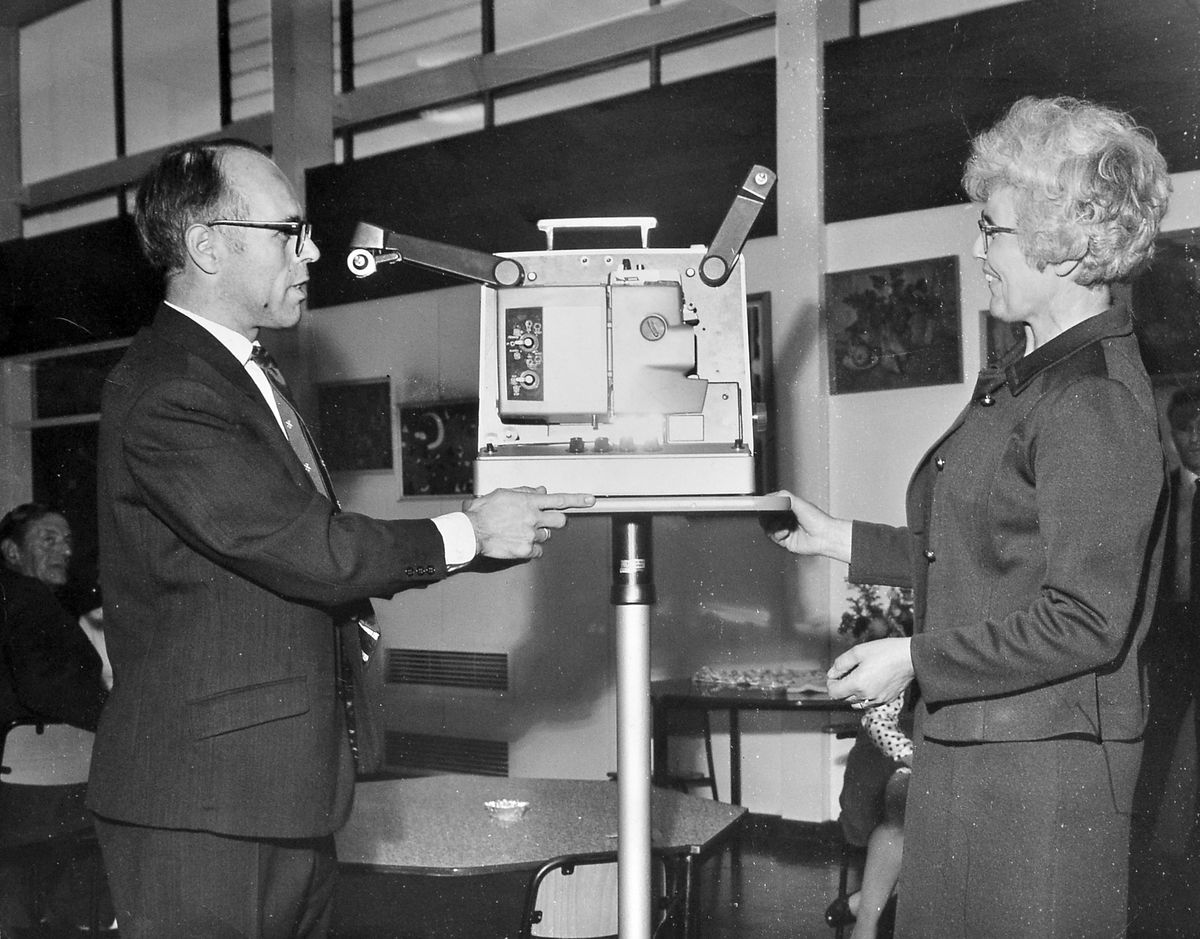 Mr C Henderson, chairman of the parent-teacher association of Dothill Junior School in Wellington, presented a film projector and accessories worth nearly £400 to the school's headmistress, Mrs J E Beard, during a social evening on July 3, 1970.