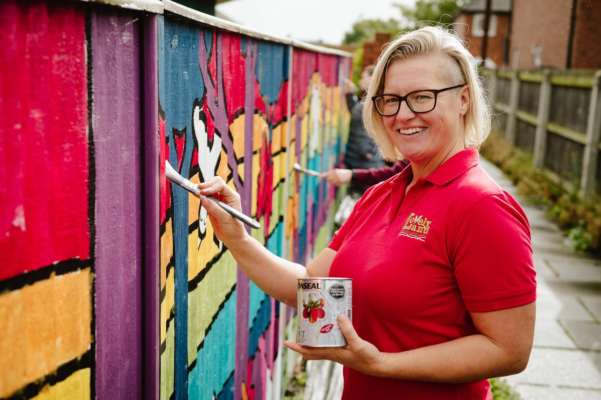 Clare Bear from Lovelyland helping to paint the mural