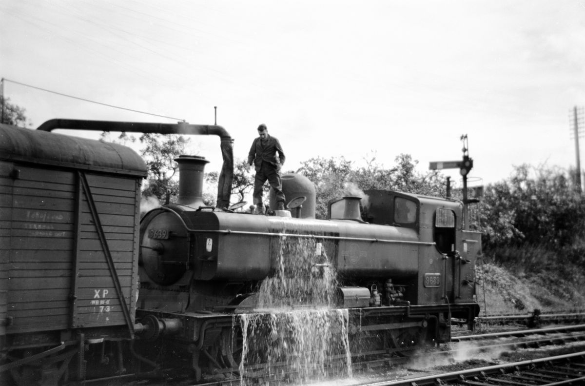 This picture taken by Les shows a steam locomotive taking on water at Market Drayton in the summer of 1963.