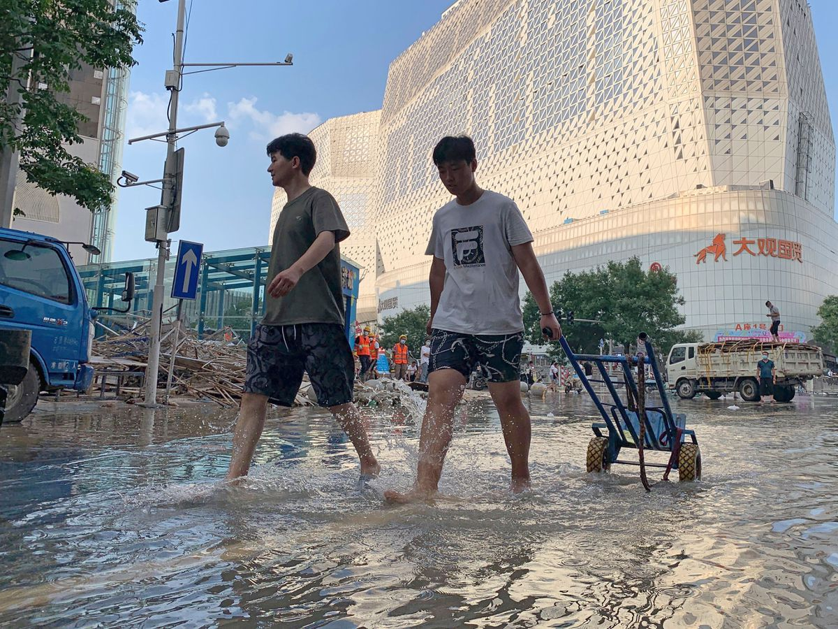 Residents walk along a flooded road