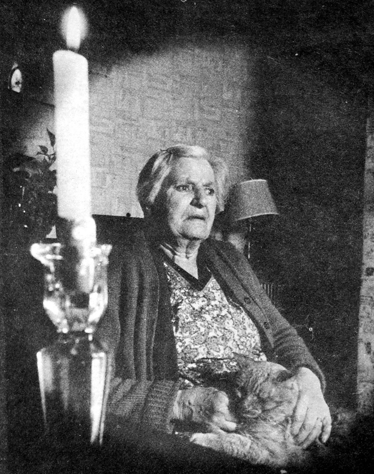 Mrs Lily Suthon, aged 73, of Madeley, resorts to candlelight during a power cut in February 1972.