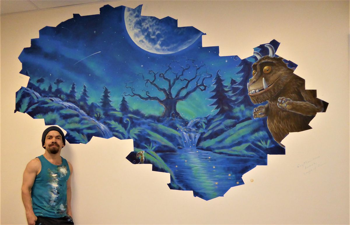 Mural artist Rory McCann with the Gruffalo mural he hand painted in the pre-operative area