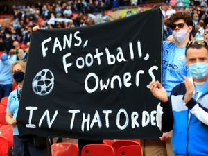 Fans hold up a banner protesting against the European Super League
