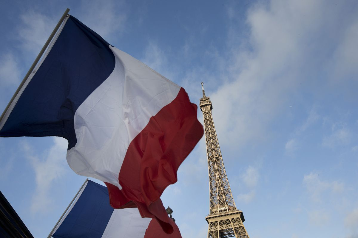 French flags fly in front of the Eiffel Tower