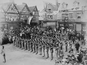 nostalgia pic. Market Drayton. Soldiers in Market Drayton firing a volley in salute. Market Drayton street scene, general view. Undated. Clearly a major occasion. 1890s? Edwardian? Note the children standing in front of the Bennion shop with their fingers in their ears.  There is also a band in the picture and the town is decorated. The wording on the banner strung up to the left includes 'God Bless' and below may start with QUE.  Unfortunately the banner on the right is draped over but one of the words seems to include the letters ...ECOR... and might be OF THE above, giving the full message something like GOD BLESS THE QUEEN OF THE ???ELOR???  or something like that, but that is just a guess. The name of the photographer on the border is R.G. Arnold. Written on the back is 'H Bloor, 26 Allen Gardens.' This picture from Mrs June Edwards, of 74 Farcroft Drive, Market Drayton, 01630 478074. margaret.edwards41@tiscali.co.uk. It is one of a number of pictures which came to her after the death of Miss Sybil Jones of Market Drayton, aged in her 80s, in early 2019. June's husband George helped Sybil's brother Terry clear the house and Terry gave the historic pictures to June and George. Sybil's partner Harold Bloor was a collector of many historic Market Drayton photos. Sybil also collected. Library code: Market Drayton nostalgia 2019..