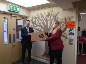 Andrew Ainge, branch principal of Nock Deighton, Bridgnorth delivering the laptop to St John's Catholic Primary School headteacher Jessica Buzzing