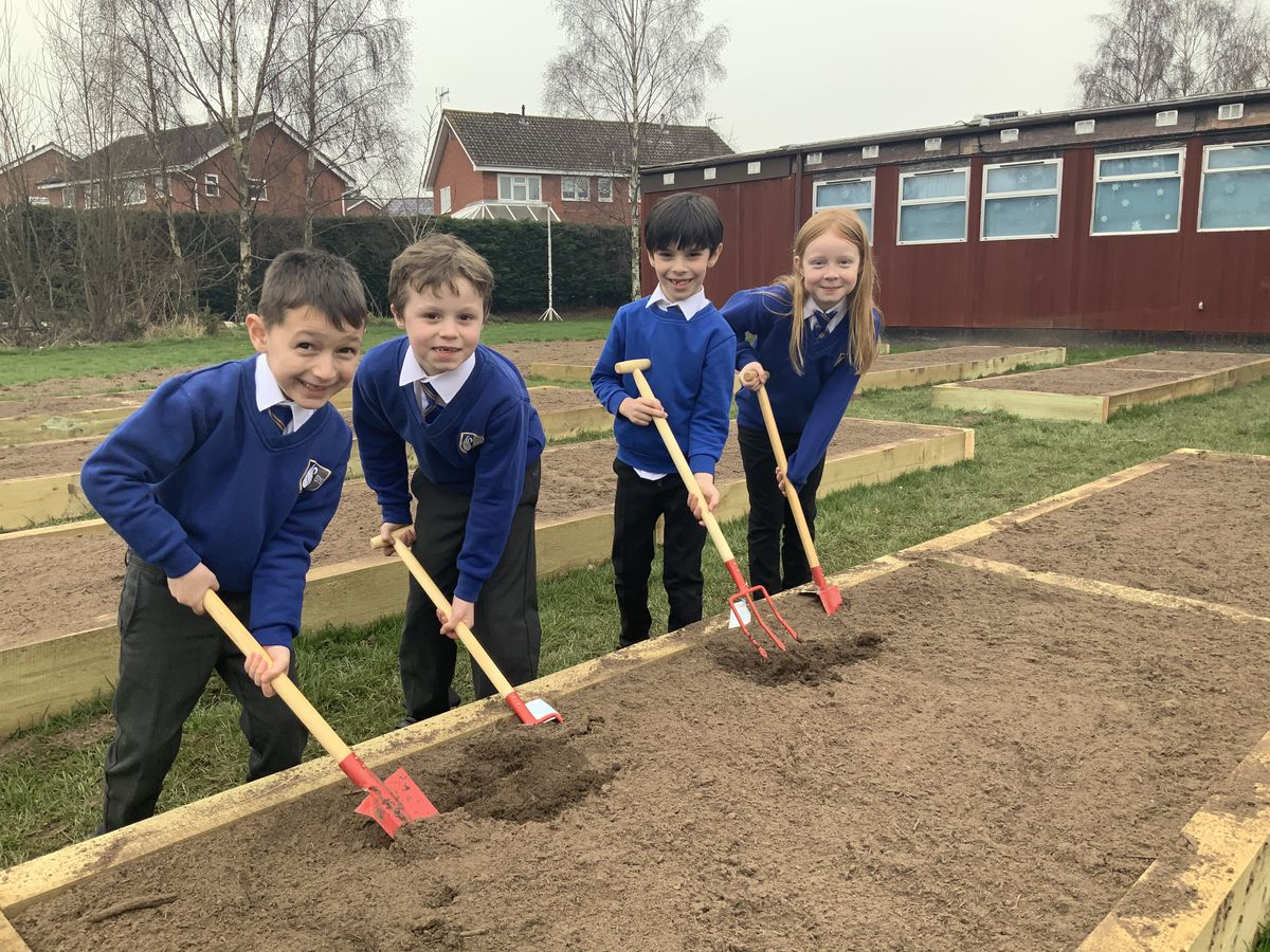 Some of the key worker children getting the allotment ready