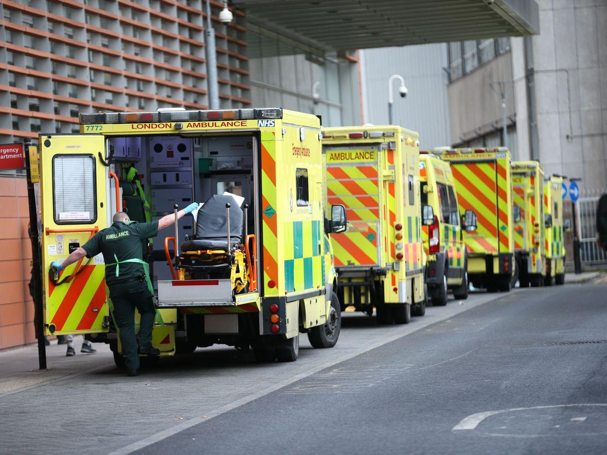 A paramedic and ambulances outside a hospital