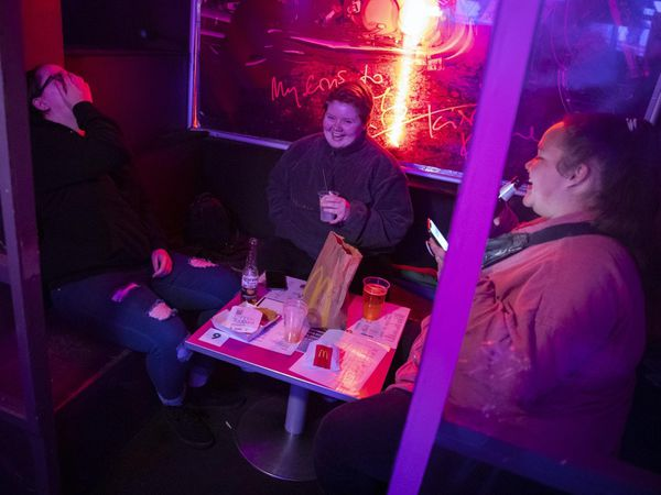 People eating McDonald's in G-A-Y bar
