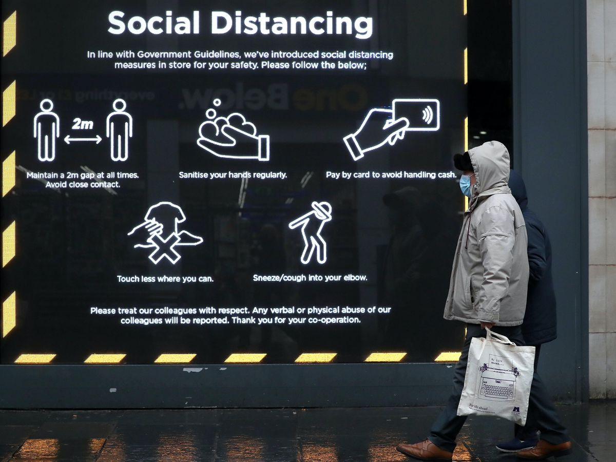 A member of the public walks passed a social distancing sign in a shop window in Glasgow
