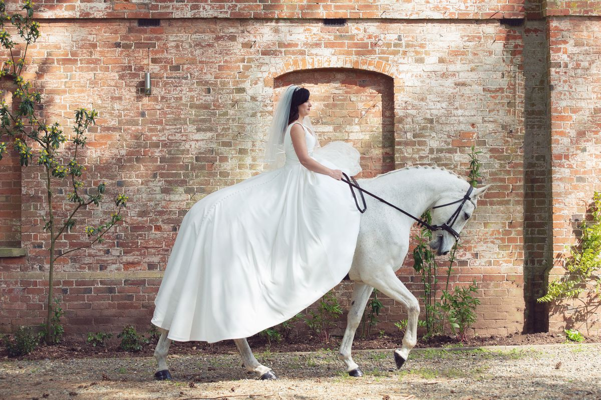 Claudia in her wedding dress atop her horse Mr T