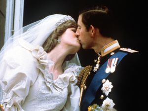 The newly married Prince and Princess of Wales (formerly Lady Diana Spencer) kissing on the balcony of Buckingham Palace after their wedding ceremony at St. Paul's cathedral