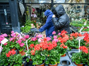 People walk past a florist as they pull their hoods over their heads in Porthcawl, Wales (Ben Birchall/PA)