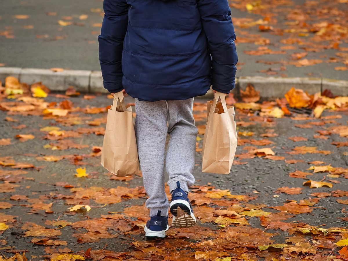 A child collects packed food parcels
