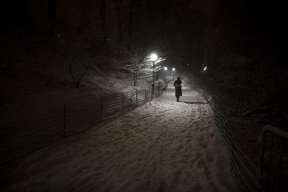 A pedestrian walks along a snowy path