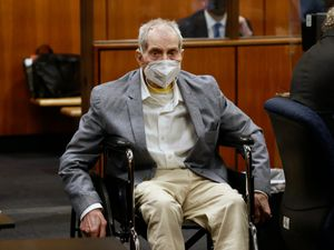 Robert Durst spins in place in his wheelchair as he looks at people in court