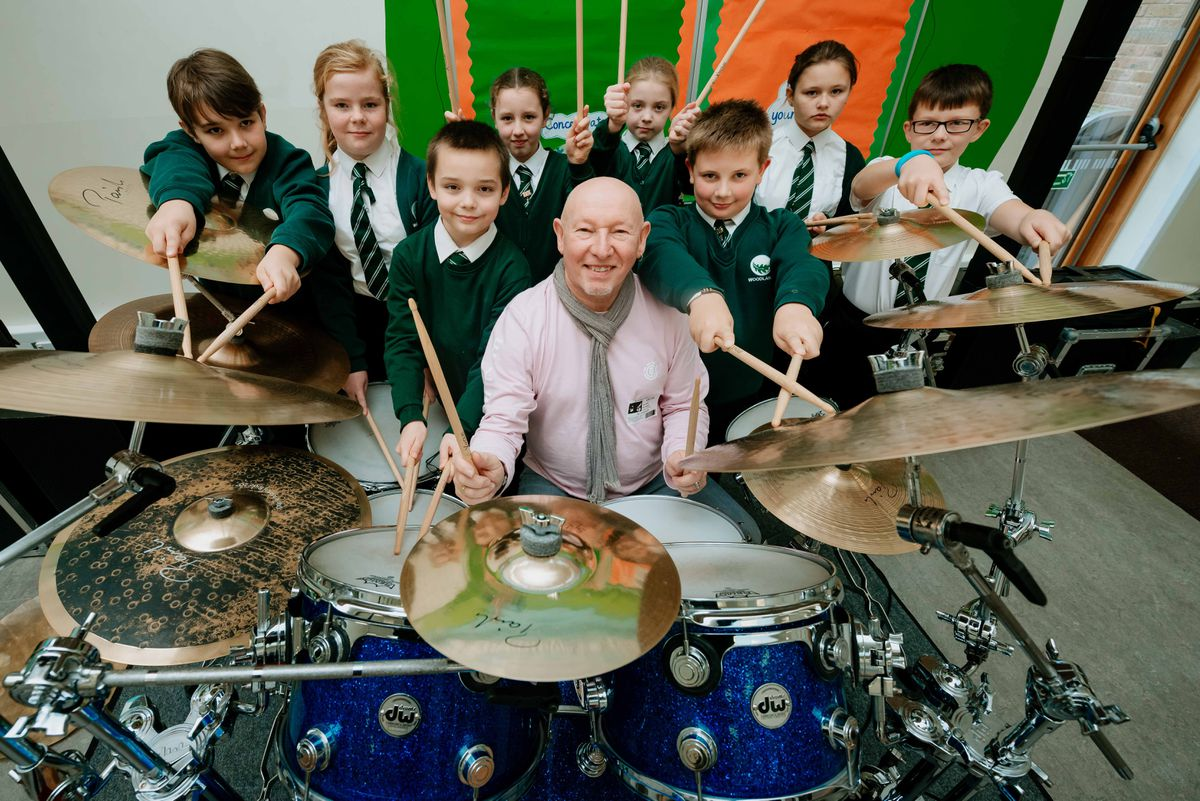 Former Status Quo drummer Jeff Rich playing the drums with pupils at Woodlands Primary School