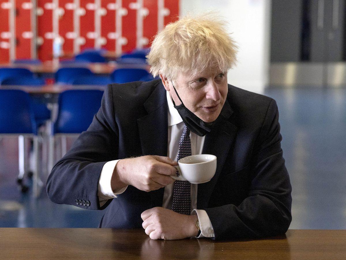 Boris Johnson drinking a cup of tea on a school visit