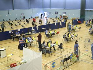 Members of the public receive a dose of the Covid-19 vaccine at the Cwmbran Stadium in south Wales