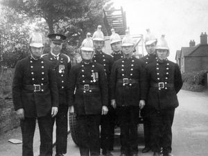 Market Drayton fire brigade in Buntingsdale Road in about 1930, complete with their open fire appliance and brass helmets. Charlie Sillitoe is on the right, and his father Henry is believed to be far left.