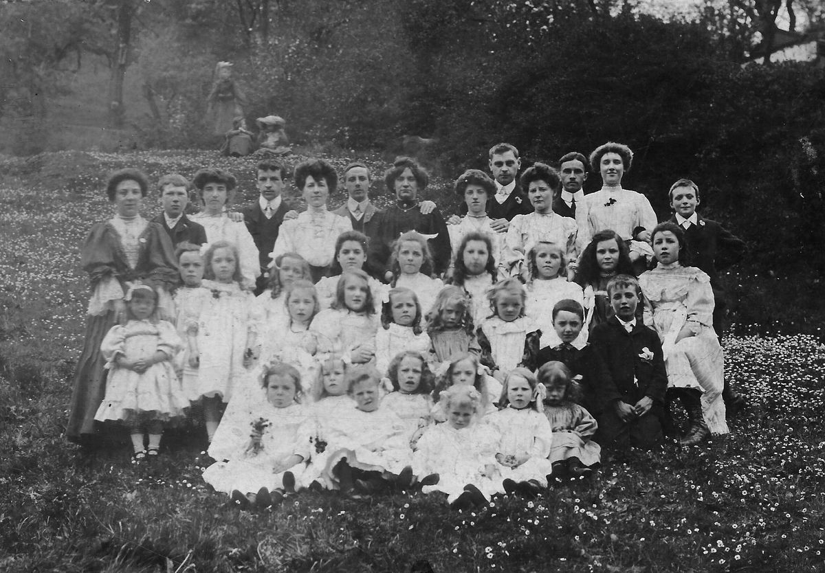 An unidentified group of children and adults in a meadow