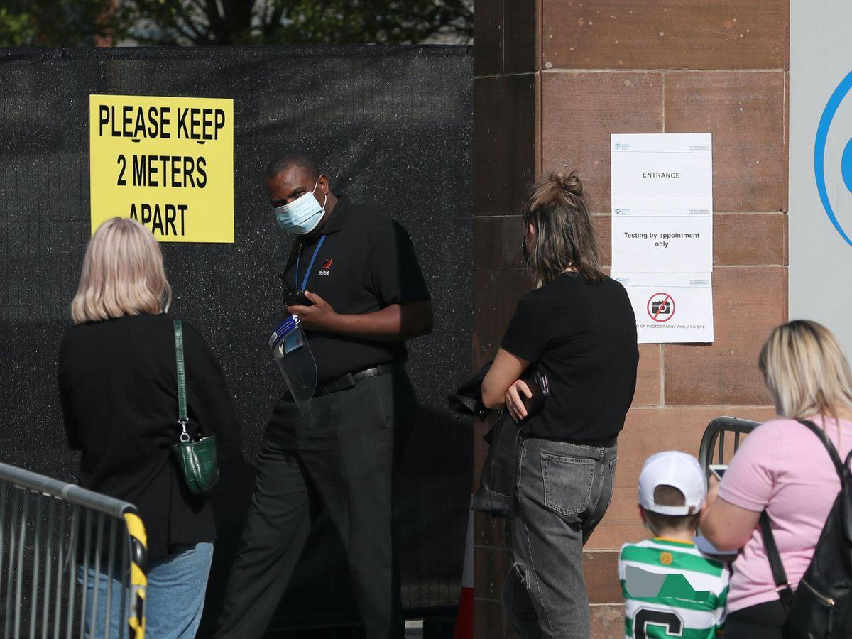 Members of the public queue outside a walk-through testing centre in Glasgow