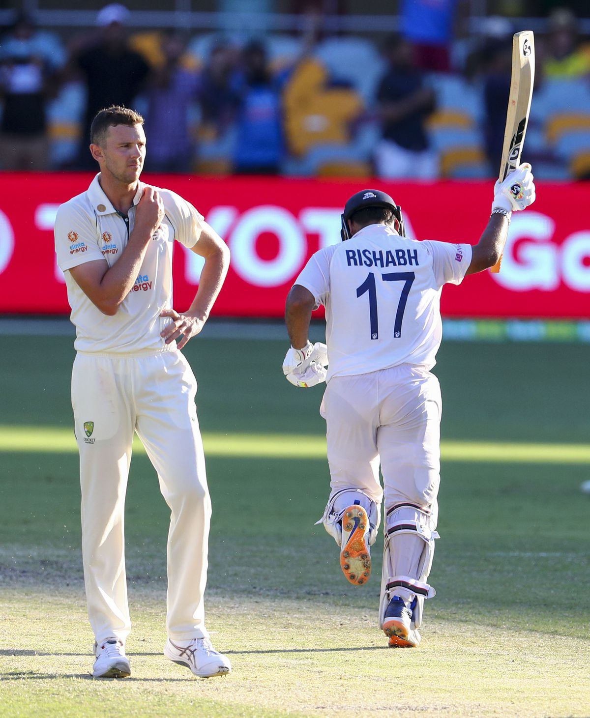 India's Rishabh Pant, right, celebrates after hitting the winning runs to defeat Australia by three wickets on the final day of the fourth cricket test at the Gabba