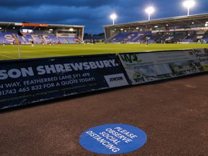 A sticker on the floor saying please observe social distancing at the Montgomery Waters Meadow Stadium the home of Shrewsbury Town during the Covid-19 Pandemic.
