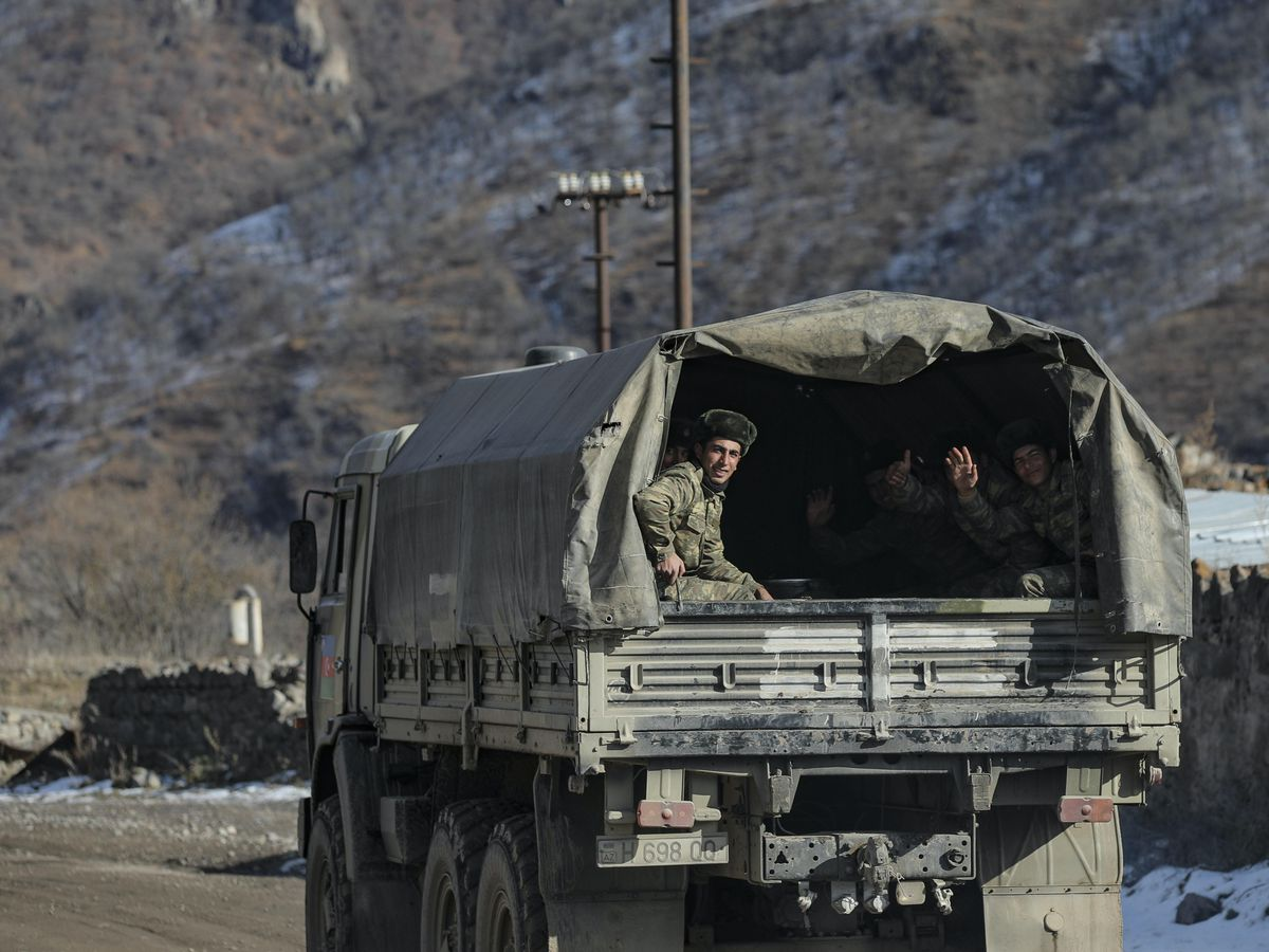 Azerbaijani soldiers sit in a military lorry on a road to their military tent camp after the transfer of the Kalbajar region to Azerbaijan's control (Emrah Gurel/AP)