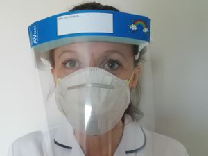 A health worker wears a visor
