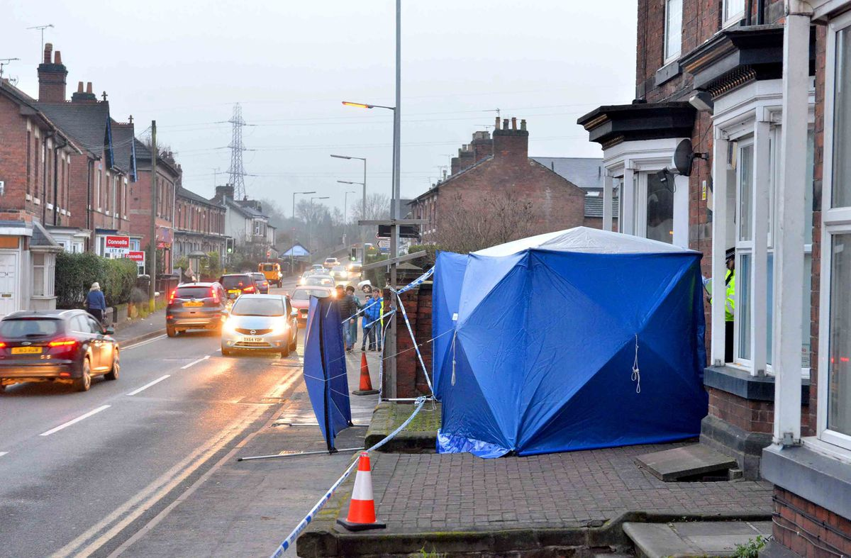 The blue tents and tape blocking the entrance to the block of flats in Stafford. Credit: Steve Leath/Express & Star