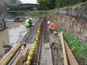 Volunteers preparing the next section of steel reinforcement for the retaining wall, showing Thomas Telford's skew bridge in the background.