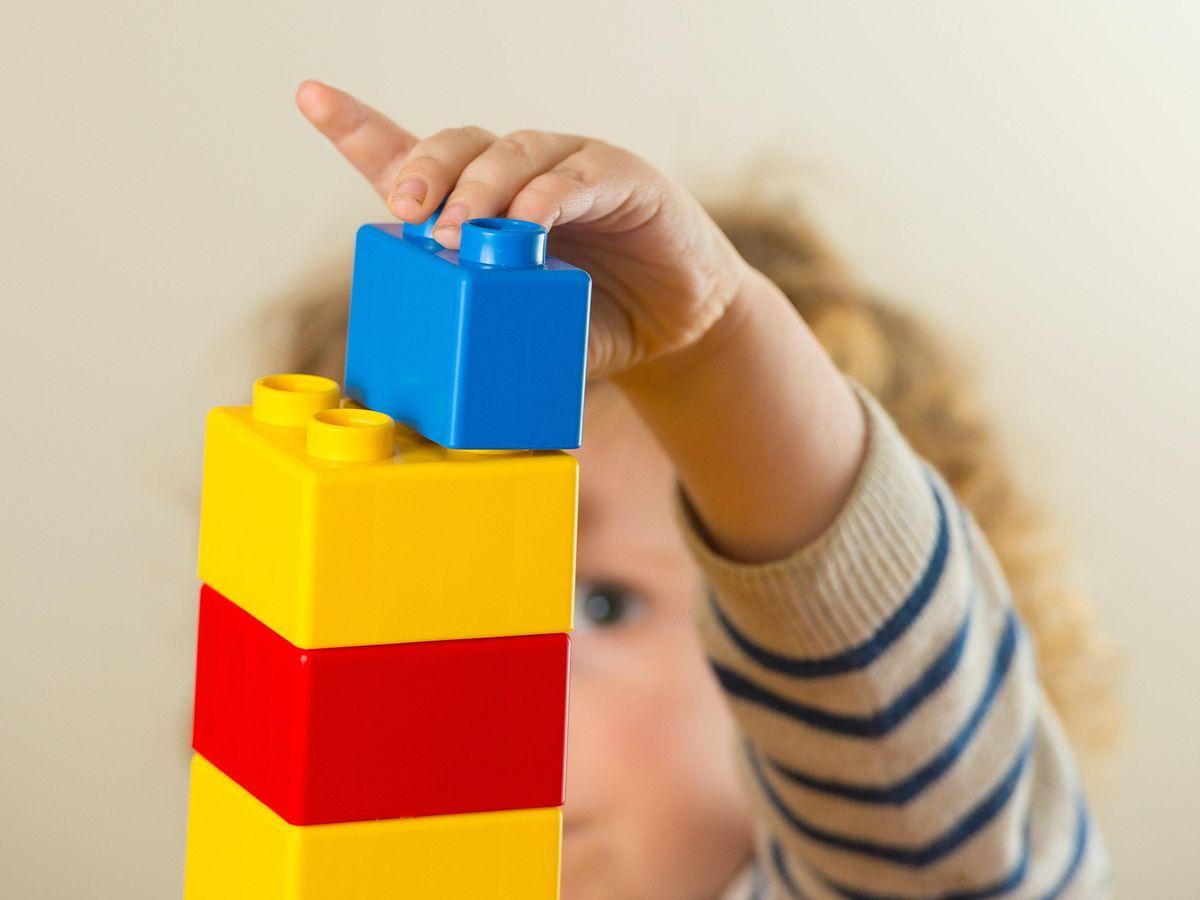 A preschool-age child plays with plastic building blocks