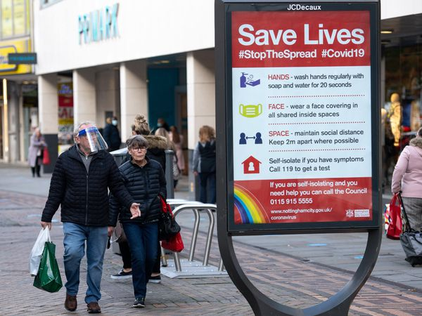 A man wearing a face shield walks past a coronavirus advice sign in Nottingham city centre