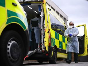 A paramedic wearing personal protective equipment exits an ambulance as the UK continues in lockdown to help curb the spread of the coronavirus