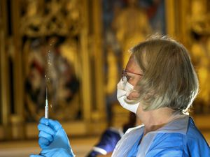 The Pfizer coronavirus vaccine is prepared by a health worker at Salisbury Cathedral (Steve Parsons/PA)