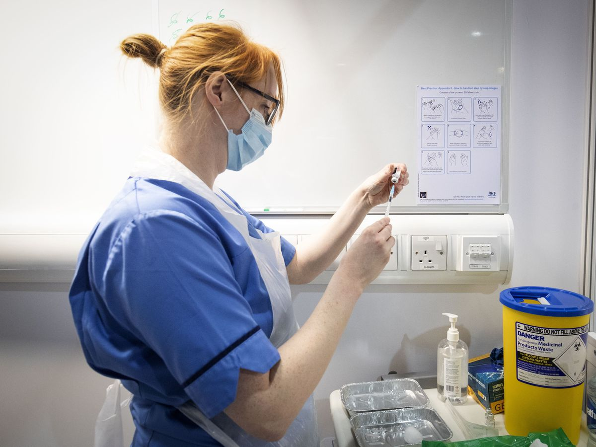 Nurse Eleanor Pinkerton prepares a coronavirus vaccine to be given to a health and care staff member at the NHS Louisa Jordan Hospital in Glasgow