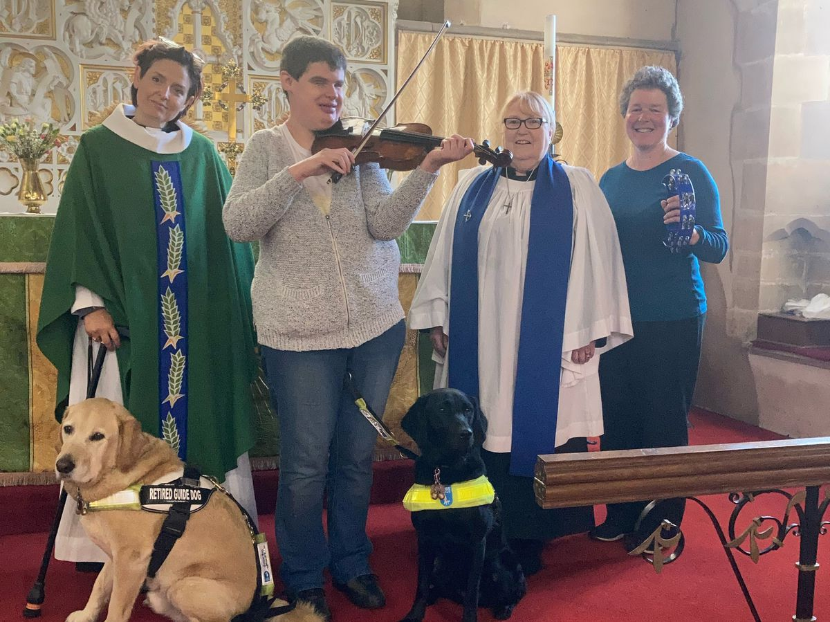 Eleanor Roberts playing the violin with her guide dog Cally, retired guide dog Woody, Reverend Zoe Hemming, Lesley Green the Churchwarden, and Liz Brown the organist/pianist