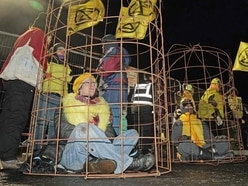 Environmental protesters dress as canaries to block entrance to mine