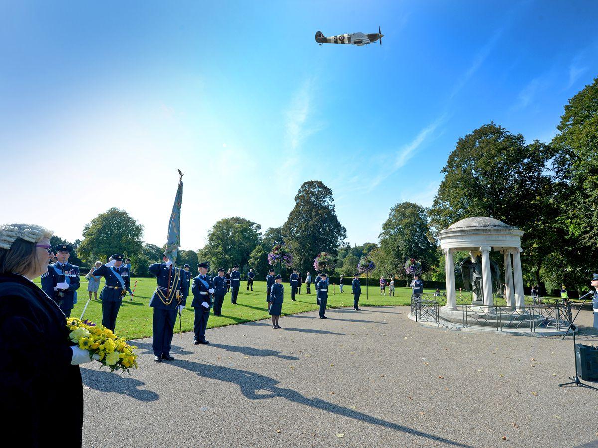 Battle of Britain ceremony at the Quarry war memorial, Shrewsbury. A spitfire flies over the ceremony