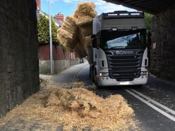 Road shut after lorry hits bridge and sheds its load of straw