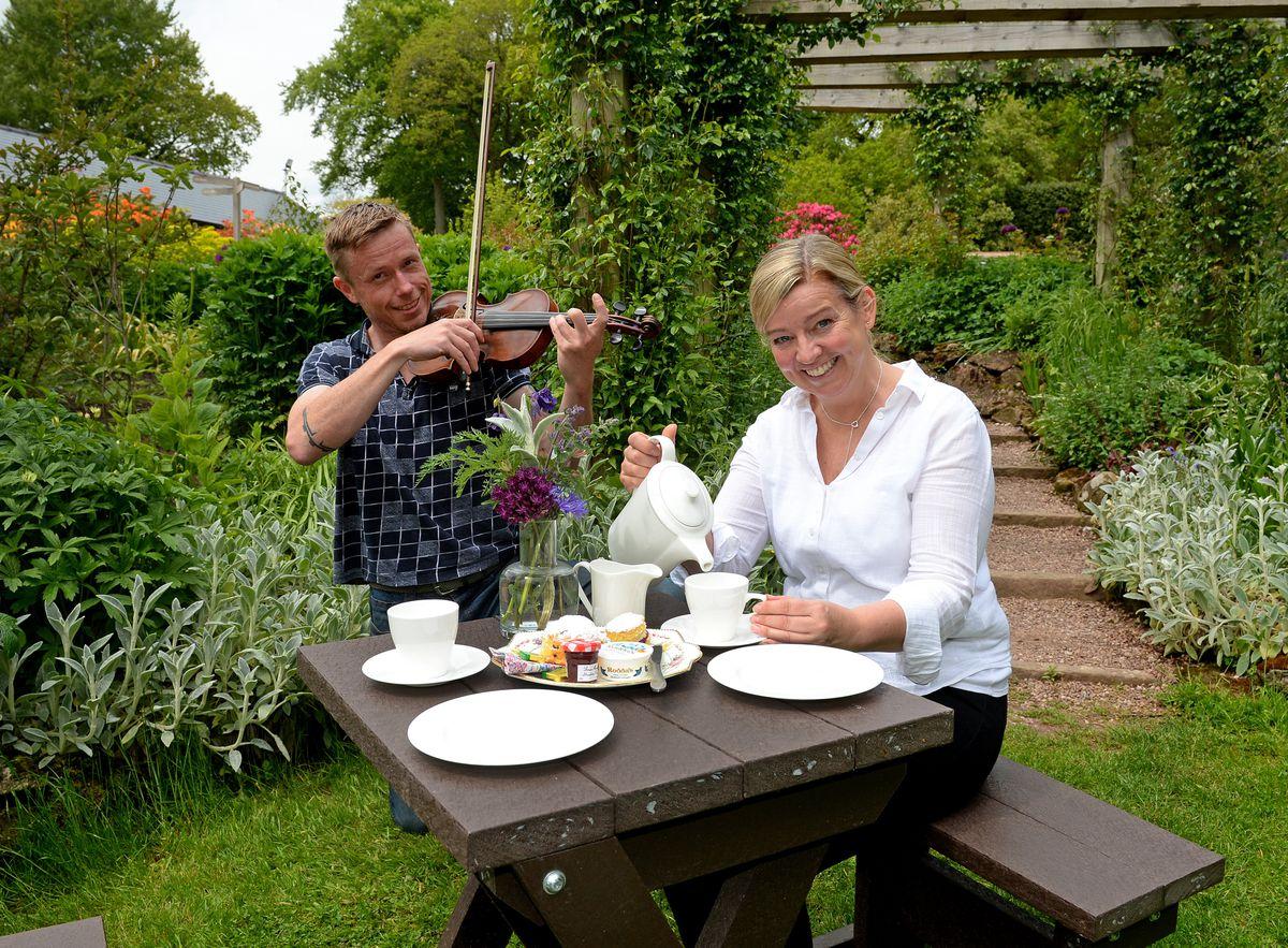 Gardener and violin player Zdenek Valkoun serenades tea room assistant Jo Lewis, as they prepare for the Quintessentially English Garden event at Dorothy Clive Garden, Market Drayton