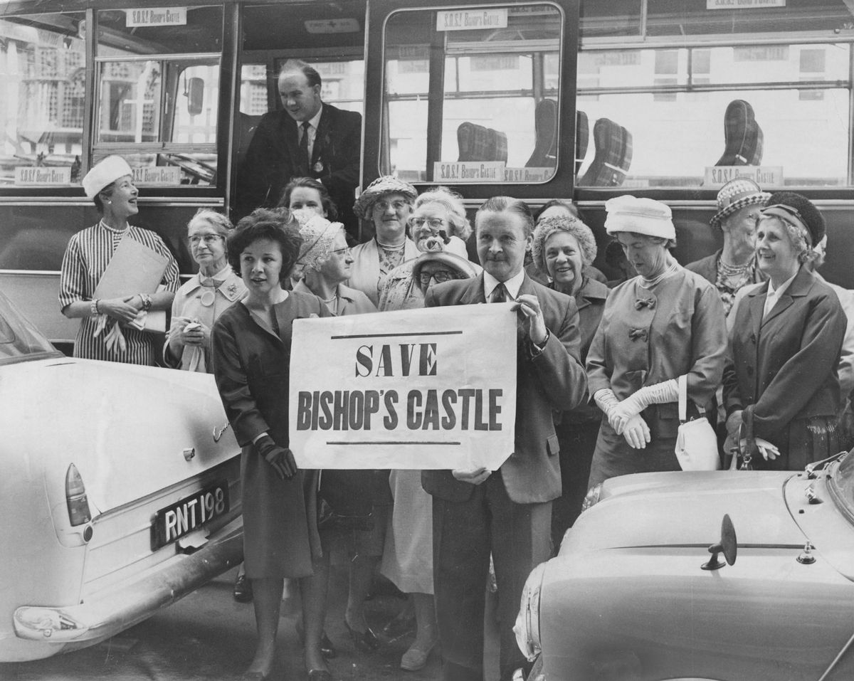 """""""Save Bishop's Castle"""" says the banner, and we heartily agree with the sentiment, as Shropshire would miss the little town. Happily the town itself was not in danger – but its council was. A big county review inquiry was starting at Shrewsbury into local government changes which would spell the end of some councils, and consequently Bishop's Castle was embroiled in a battle to save its independence. This delegation arrived on a battle bus at the Shirehall. Holding the banner is Bishop's Castle deputy mayor, Councillor W H Jarvis, with his 16-year-old daughter Gwyneth. We're pretty sure the date is June 30, 1964."""
