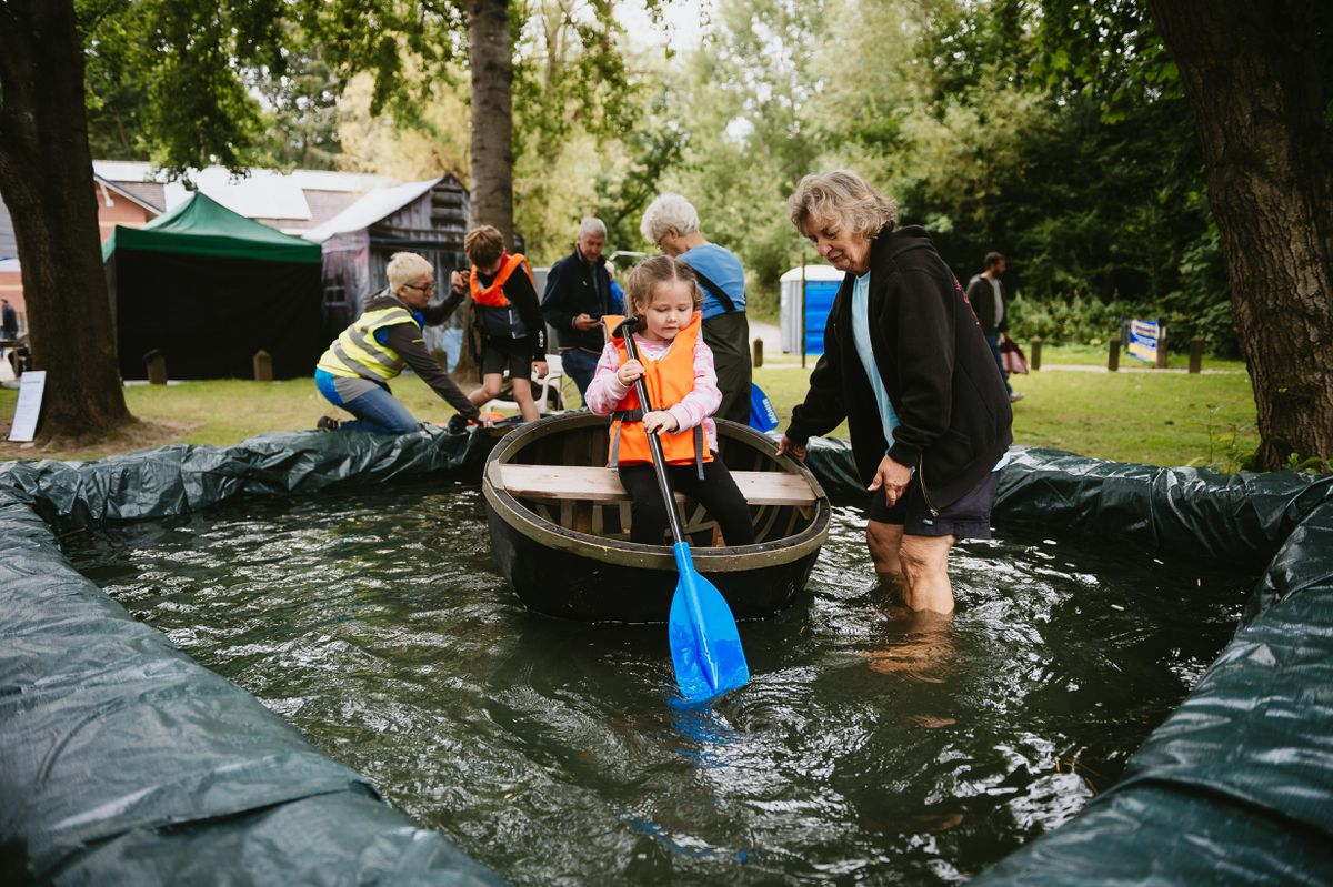 A youngster has a go in a coracle in the paddling pool.