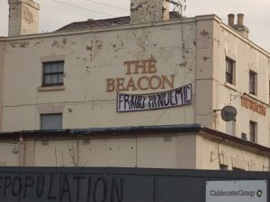 """A """"fraud pandemic"""" banner hung on the closed Beacon pub in Madeley"""